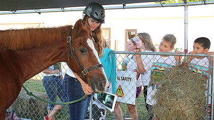 The Marion County Extension Office held its first annual Marion County Progressive Agriculture Safety Day on Thursday, Sept. 24, at the Marion County Fairgrounds. Fourth grade students from across the county attended the event, which educated them about a variety of topics, including animal safety, ATV safety, electrical safety, farm equipment and tractor safety, water safety, fire arm safety, first aid, grain bin safety, food safety and the dangers of drugs. Marion County High School FFA student Alexis Hayden talks to students about animal safety, specifically related to horses.