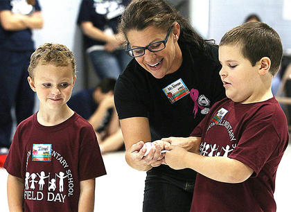 "West Marion Elementary School student Israel Medley, special education teacher Shelly Peterson and Wyatt Raikes, also a WMES student, participate in the ""eyeball/spoon race."""
