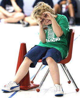 Ryker Wiser, a student at Calvary Elementary School, puts on his fake binoculars as he takes a break from the action.