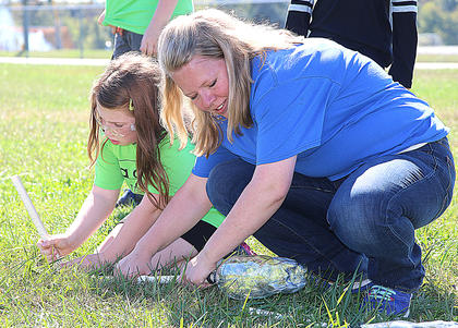Rebecca Hill, Marion County Extension Agent for 4-H Youth Development, assists Jenna Mullins during her rocket experiment.