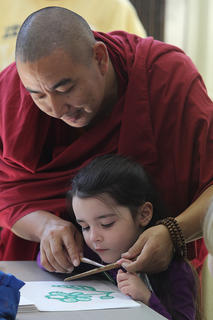 Yeshi  Nyingdak shows Hannah Wheeler how to use the chakpurs to create sand art during a children's art class.