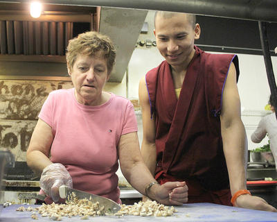 Jody Mattingly minces mushrooms during a cooking class Oct. 9 at The Stillhouse as  Tenpa Dawa gives a smile.