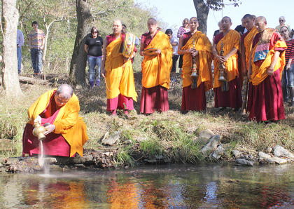 Lama Kunzang Tenphel pours the sand used to make the mandala into the waters at Pope's Creek Ranch.