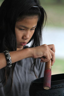 Tessa Mei-Li Hillman plays with a bowl for sale by the monks during a potluck picnic Oct. 13.