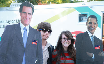 Trip Foxworth and Catie Gregg of Georgetown pose for a photo between cardboard cutouts of Republican Presidential candidate Mitt Romney and President Barack Obama.