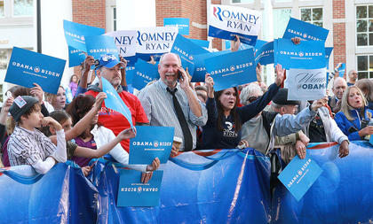 Obama and Romney supporters jockey for position in hopes of appearing on the MSNBC cameras.