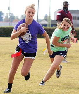 Sophomore Savannah Goode carries the ball with her eye on the end zone while Louise Lavin tries to catch up with her. The juniors were victorious over the sophomores.