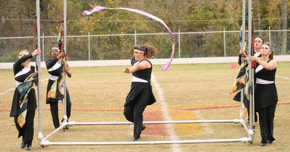 Ariel Bright dances inside the box as her fellow color guard members, Dallas Dowell and Jarie Newby (on the right) and Katie Elmore and Leslie Smothers move in sync.