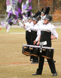 Trent Fenwick plays the drums as Corinna Benningfield and Andrea Ackerman add some color to the Marching Knights performance.