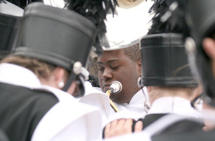 Tyler Smalley joins his bandmates in a prayer before they head to the field for their performance Saturday.
