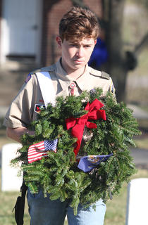 Steven Duffee, representing Boy Scout Troop 616, presents a flag in honor of the United States Merchant Marines.