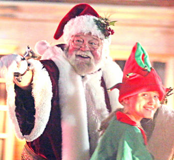 Santa Claus waves to the crowd during the Dickens Christmas Parade. Also pictured is his adorable elf.