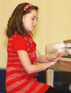Aubrey Mealy concentrates as she plays the piano.