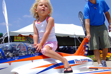 Ella Grace Ritsko, 2, of Gray, Tenn., goes for a ride on her father's model jet. Ed Ritsko is pushing the jet.