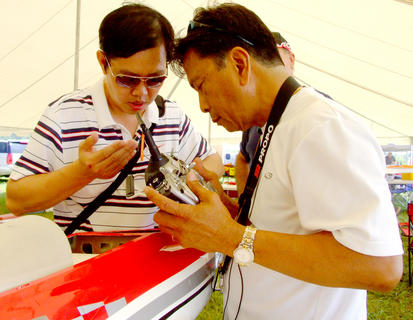 James Chan, left, helps Eddie Lozano of Silver Springs Maine make some adjustments to his plane.