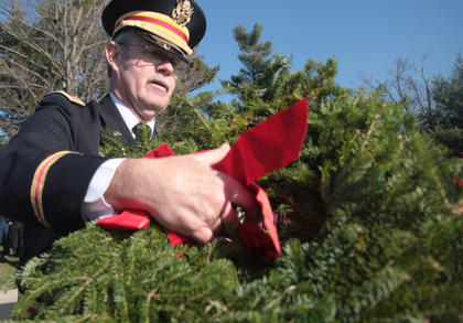Mike Andrews of the Marion County Veterans Honor Guards helps distribute wreaths to be placed at the gravesites.