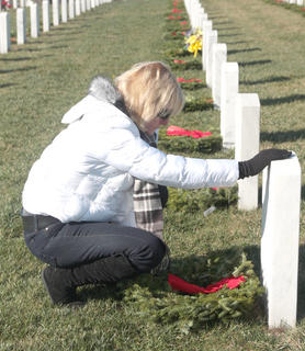 Denise Chatigny takes a moment to think about the veteran buried in the gravesite where she placed a wreath.