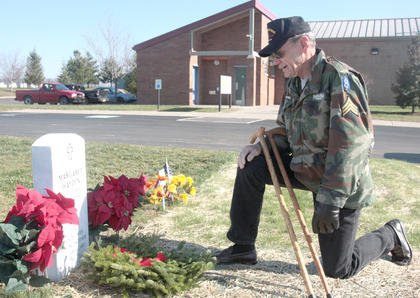 Jerry Hayden, a Vietnam Veteran, takes a moment at his wife's gravesite after their son placed a wreath.