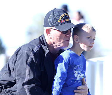 Veterans Day was celebrated at the Lebanon National Cemetery on Sunday. A Michael and Jackson Dowell listen to Terry Wooley play the guitar.