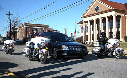 The funeral procession drove past the David R. Hourigan Government Building on the way to the cemetery.
