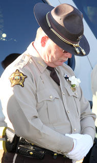 Sheriff Jimmy Clements bows his head during the graveside service.