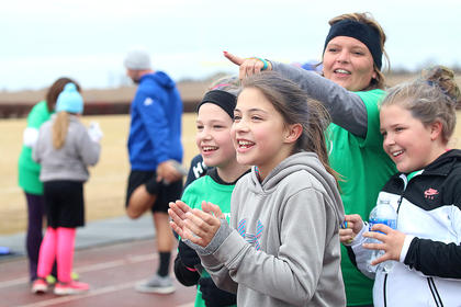 Lebanon Middle School Heart & Sole participants huddle together to try and stay warm in the cold temps and a bitter cold wind Saturday morning as they cheer on their teammates. Pictured are Brianna Knopp, Laura Thomas, Abigail Spalding and her mother and Heart & Sole Coach Casey Spalding.