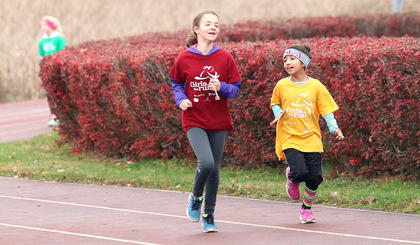 Anna Allan, left, and Julianna Dixon, both students at St. Augustine Grade School, run together and chat to help make the miles go by faster.