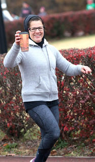 Shelly Peterson enjoys a cup of coffee as she runs a lap around the track.