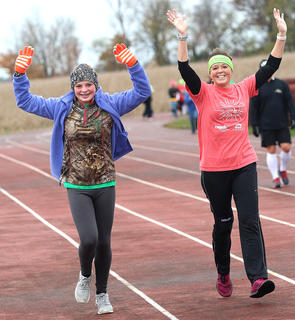 """Emily Spalding, left, and Sharon """"Sam"""" Bach, throw up their hands for the camera as they complete another lap around the track. Spalding is a Heart & Sole participant at Lebanon Middle School."""