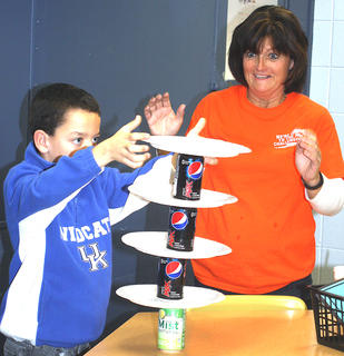 Samuel Thompson attempts to stack a tower of soft drink cans as West Marion Elementary School teacher Debbie Burdette anxiously watches.