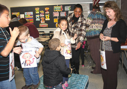 """Paula Walston, a fourth grade teacher at Lebanon Elementary School, leads an activity where children were """"monkeys jumping on the bed."""" Also pictured are, from left, Lorenzo Venegas, Blake Wise, Melachhi Mattingly and Geraldine Garcia-Gongora."""