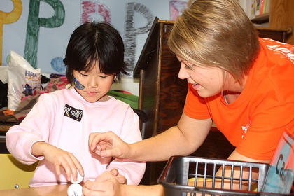 West Marion Elementary School teacher Jessica Hutchins helps a student with an activity.