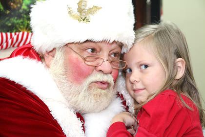 Kinzleigh Broyles, 3, snuggles up to Santa Claus as she prepares to tell him what she wants for Christmas.