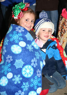 Cousins Molly Mattingly, left, and Conrad Jenkins stay warm underneath a blanket while listening to local children sing Christmas carols Friday evening at Dickens Christmas in downtown Lebanon.