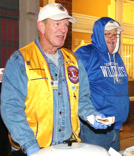 Lebanon Lions Club President Jerry Lanham and Terry Mattingly, fellow Lions Club member, serve free hot dogs and cookies at Dickens Christmas. The Lions Club served more than 400 hotdogs Friday evening.