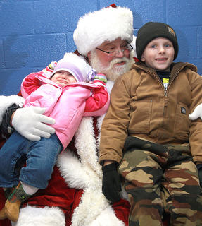 Kinzleigh Broyles, 10 months, isn't quite as happy to see Santa as her brother, Caden, 7.