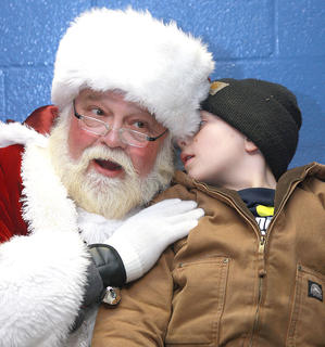 Caden Broyles, 7, whispers want he wants for Christmas into Santa's ear.