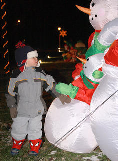 Kooper Jones, 2, takes a closer look at an inflatable featuring a family of snowmen.