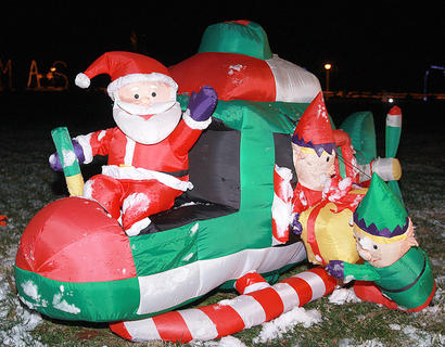 Santa waves while elves pack his helicopter in this inflatable.