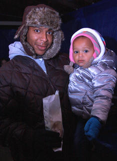 Aaron Brown and his daughter Zariyah, 1, enjoy some popcorn and some warmth under an enclosed pavilion before Santa arrives.