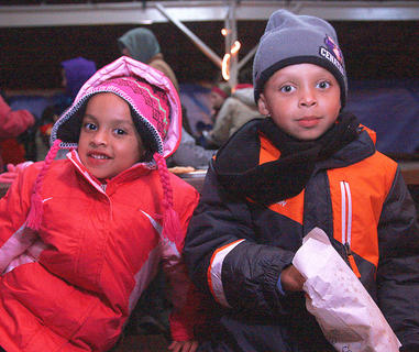 Siblings Adriana Brown, 4, and Rashaud Brown, 6, huddle together while waiting for Santa to arrive.