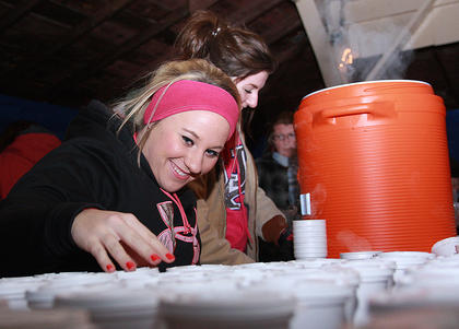 Caroline Peterson (headband) sets out hot chocolate as soon as Emma Thompson can get them ready.