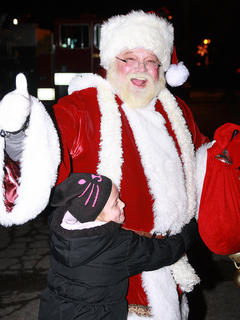Santa is greeted with a big hug from Vanessa Van Why, 7, after arriving on a fire truck.