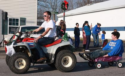 Shawn Crabtree (driving the ATV) pulls Nathan Mink in a wagon along the parade route.