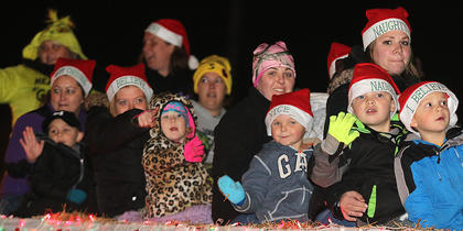 A wagon full of children wave to the crowd during the Loretto Christmas Parade Friday evening.