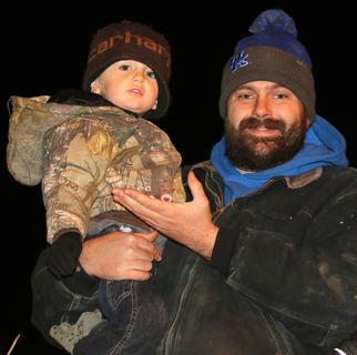 Patrick Smith holds his nephew Thomas Hall on Loretto Lumber's float in the parade Friday evening. Thomas' parents are Farland and Amanda Hall.