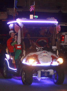 Fred and Mary Rita McClure give a ride to Gracie Raikes (7), Joshua Raikes (5) and Mia Vermeire (1) in a decorated golf cart.