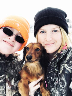 Brandon Estes and Tammy Washburn pose for a photo in the snow with their dog, Butterball.