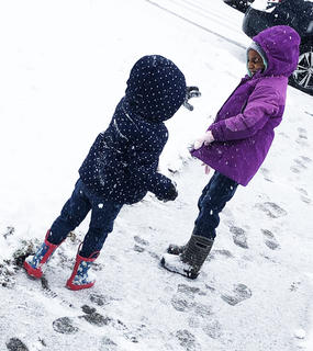 JahNiah Porter (purple) and her sister ZaRiah Porter enjoy the snow day by having a snow ball fight.