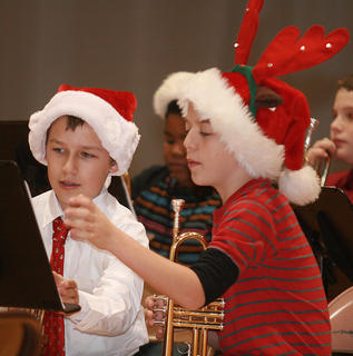 The Marion County middle school band performed a Christmas concert Dec. 11 at Lebanon Middle School. The performance included classic carols, and a few familiar tunes with re-imagined names, but the musicians got in the spirit with their attire. Camden Stiles, left, and Samuel Thompson review their music before the concert.